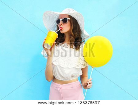 Fashion Pretty Woman In Straw Hat With Air Balloon Drinks Fruit Juice From Cup Over Colorful Blue Ba