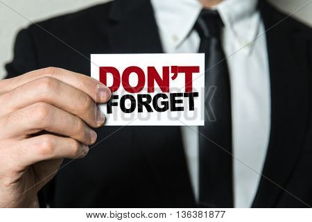Business man holding a card with the text: Don't Forget