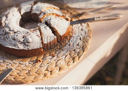 The cake strewed with icing sugar on a table. Freshly baked sweet cake. Festive breakfast. Breakfast outdoors. Festive lunch outdoors. Festive dinner outdoors.Freshly baked sweet cake closeup . Baking on a table. Summer dinner outdoors.