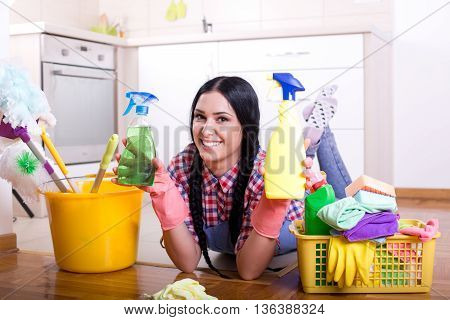 Girl Showing Spray Bottles In Kitchen