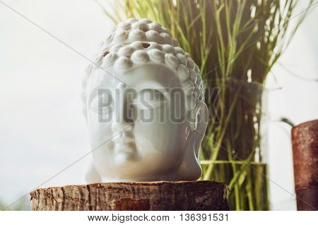 Zen spiritual ritual meditating white face of Buddha brown candle on green floral background. Religion concept esoterics. Still life rustic style. Home decor. Place for text copy space