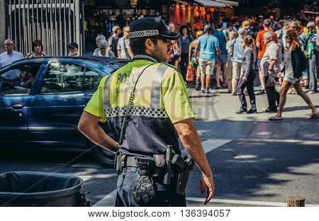 Barcelona Spain - May 28 2015. Policeman stands next to market called La Boqueria foremost tourist landmarks in Barcelona