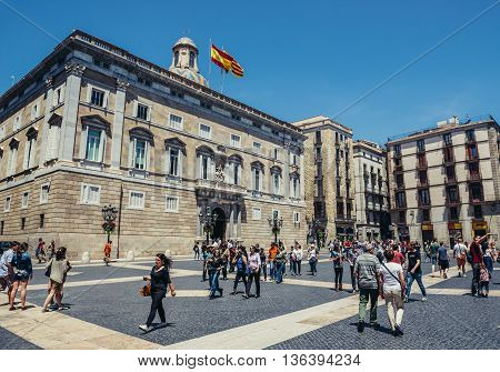 Barcelona Spain - May 28 2015. Tourists and local residents walks at St Jaume Square in front of building of Palace of the Government of Catalonia