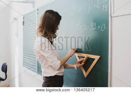 Smart student or teacher drawing mathematic formula at blackboard, dressed in university uniform, scribbled with chalk - formulas and drawing. Concept of intelligent and scientist woman.