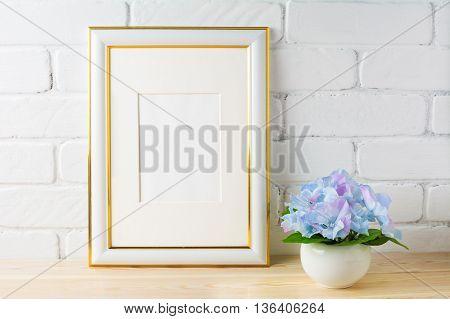 White frame mockup with blue hydrangea. Empty white frame mockup for design presentation. Portrait or poster white frame mockup for artwork promotion.