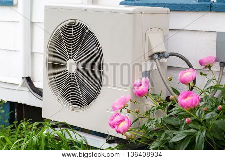 Air conditioning/ Heat pump unit on the side of a home among the flowers.