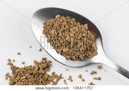 Close focus on premium brown decaf coffee power putting on stainless steel teaspoon and white background