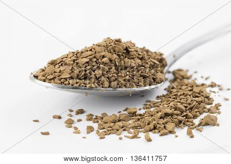 Close focus on premium brown decaf coffee powder putting on stainless steel teaspoon and white floor which isolated on white background