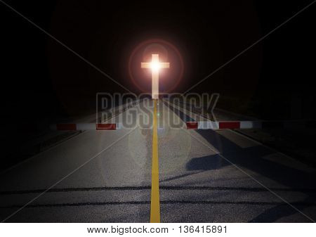 Red barricade at stop area with crucifix or cross at the end of road barrier or blackade with long road with crucifix light in darkness