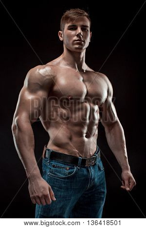 Muscular bodybuilder guy doing posing over black background. Naked torso in jeans. He looks into the camera poster
