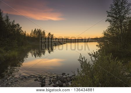 Sunset on calm and noiseless lake in Finland.