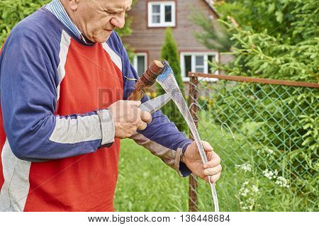 Senior man sharpening a scythe with grindstone in front of his summer house in the background