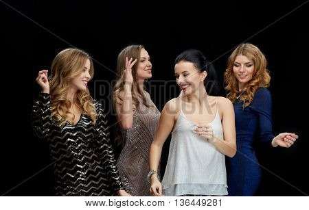 party, holidays, nightlife and people concept - happy young women dancing at night club disco over black background