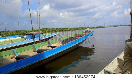 Thai longtail boats lined up at Thale Noi lake for tourists to rent, Thailand, seen from another boat,