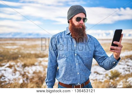 bearded hitch hiker using smartphone to look up directions