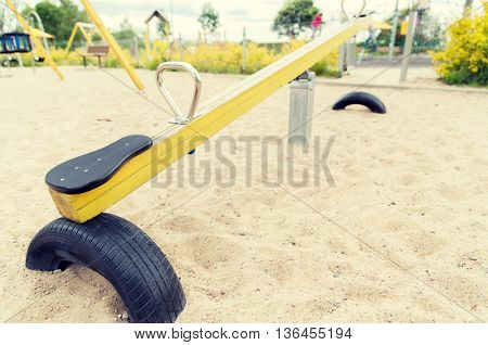 childhood, equipment and object concept - close up of swing or teeterboard on playground outdoors