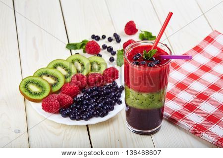 Berry smoothie.Fresh summer cocktail.Blueberryraspberrykiwi.Vitamin A. Vitamin C.Checkered napkin.On white wooden table with ingredients.Healthy lifestyle.Diet and weight loss concept.Top view