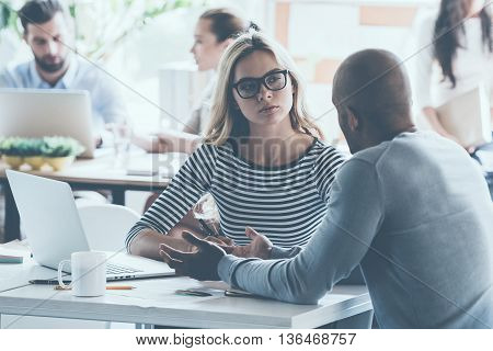 Discussing business. Two young business people discussing something while sitting at the office desk together while their colleagues sitting in the background