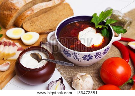 Traditional ukrainian meaty borscht on the table with ingredients