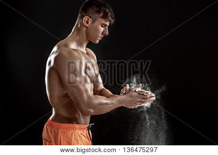 young muscular man preparing to hand lifting heavy weight. White talcum dynamically scatters in different directions. stands sideways