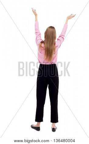 Back view of  business woman.  Raised his fist up in victory sign.    Raised his fist up in victory sign.  The girl office worker in black trousers held up her hands to heaven.