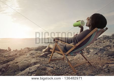 Thirsty woman drinking at the beach