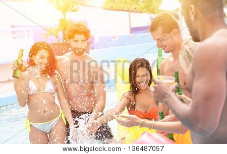 Group of multi ethnic friends having party in pool drinking cocktail and beer - Young people laughing and smiling outdoor in summer time - Vacation and friendship concept - Soft focus on left guy