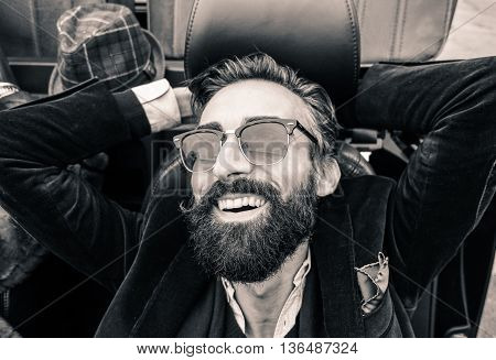 Fashion portrait of young bearded man ready for road trip - Cheerful hipster guy sitting in car lokking the sky - Black and white editing - Soft focus on beard - Warm vintage retro filter