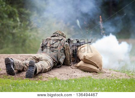 german soldier fires with rifle through smoke grenades