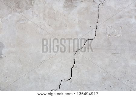 Gray plaster cracked wall texture with diagonal crack