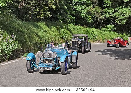 PASSO DELLA FUTA (FI) ITALY - MAY 21: driver and co-driver on an old racing car Aston Martin Le Mans (1933) in historical classic car race Mille Miglia on May 21 2016 in Passo della Futa (FI) Italy