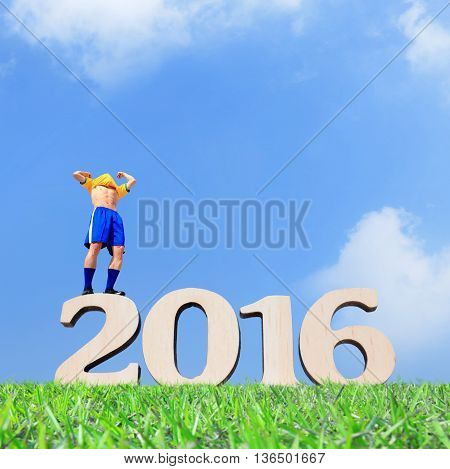 Excited Soccer player man and stand on the 2016 text with blue sky