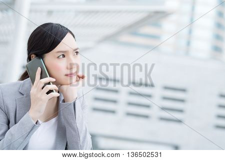 unhappy business woman speak smart phone in office asian beauty