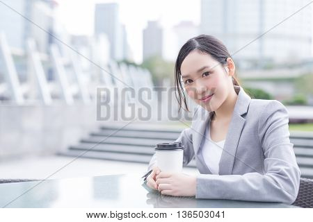 business woman sit and hold coffee cup with office background asian shot in Hong Kong