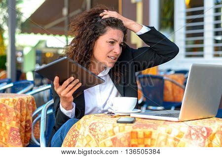 Perplexed stressed young businesswoman holding her hand to her hair and frowning at her laptop computer as she sits at a restaurant table outdoors
