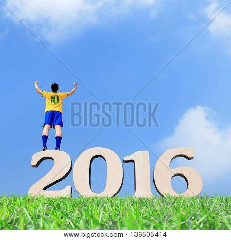 Brazil soccer player man stand on the 2016 text with blue sky