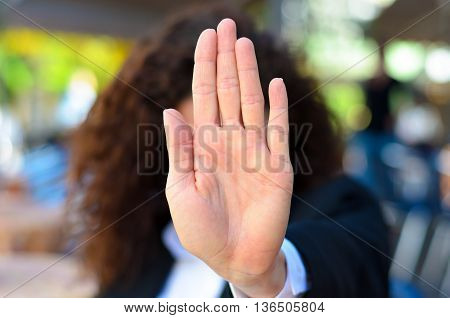 Woman giving the halt or stop sign holding up her palm in an authoritative manner indicating she has had enough no access or halt immediately