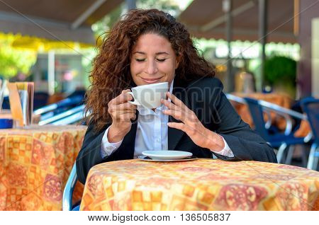 Blissful attractive stylish young woman savoring the aroma of her coffee with closed eyes and a beaming smile as she sits at a table at an outdoor cafe