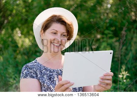 woman in a hat with pc tablet outside