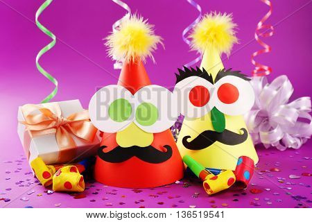 Funny party hats with blowers on color background