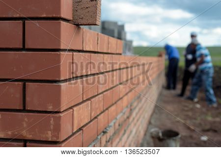 Newly built red brick wall of a newly built house with bricklayers in the background