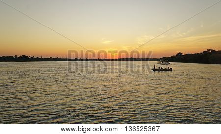 Sunset on the Zambezi River in Zambia, boats in the evening sun