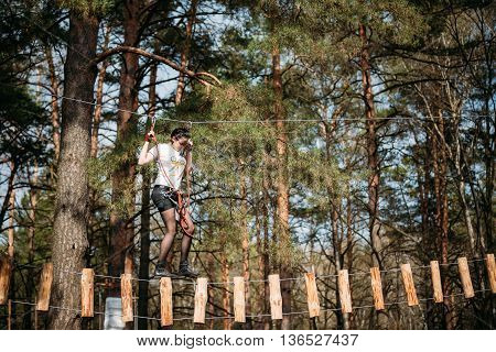 Gomel, Belarus - April 10, 2015: Young woman in park clambering with ropes in forest.