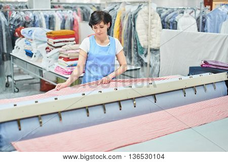 Woman Laundry worker pats the linen on the automatic machine at the dry cleaners poster