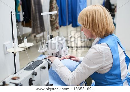 The Laundry worker performs repair of clothing on the sewing machine at the dry cleaners