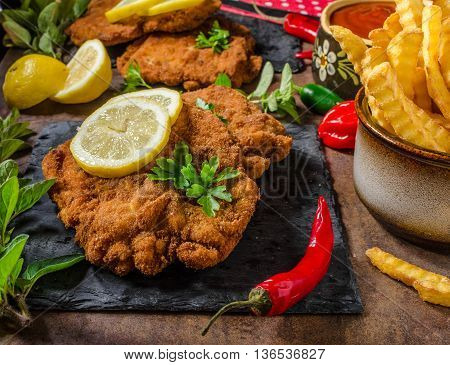 Schnitzel With Fries, Salad And Herbs