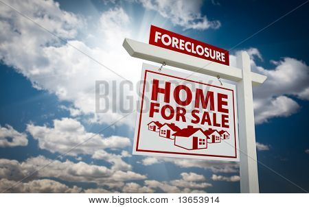 White and Red Foreclosure Home For Sale Real Estate Sign Over Beautiful Clouds and Blue Sky.