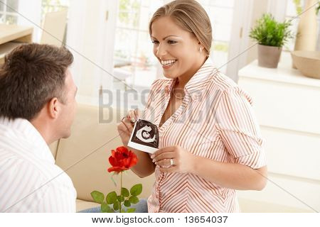 Happy pregnant woman holding baby's ultrasound image, smiling at man giving red rose in sitting room.?