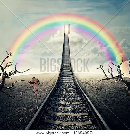 Railway of opportunity along a cracked desert ground with dry trees going up as a staircase to a opened door over the rainbow in the sky. Road to success symbol. Business plannig concept