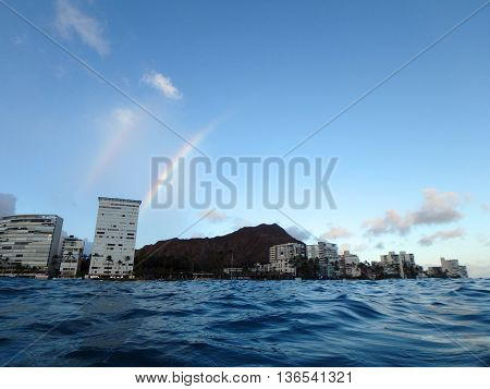 Double Rainbow over Hotel building Outrigger Canoe Club coconut trees Condo buildings clouds and Diamond Head Crater in the distance on Oahu Hawaii viewed from the water on a beautiful day.